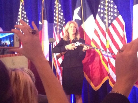 Wendy Davis holding shotgun on stage