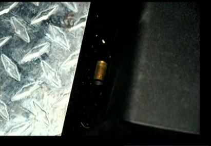 (Shell casing on floor by driver's seat, Dunn's car.)