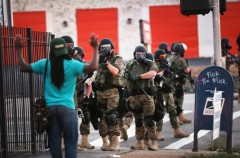 Heavily armed police making arrests in early days of Ferguson rioting.